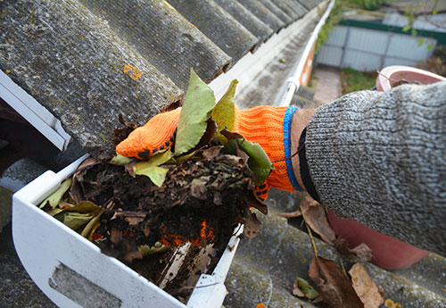 man wearing gray sweater and orange gloves cleaning gutter